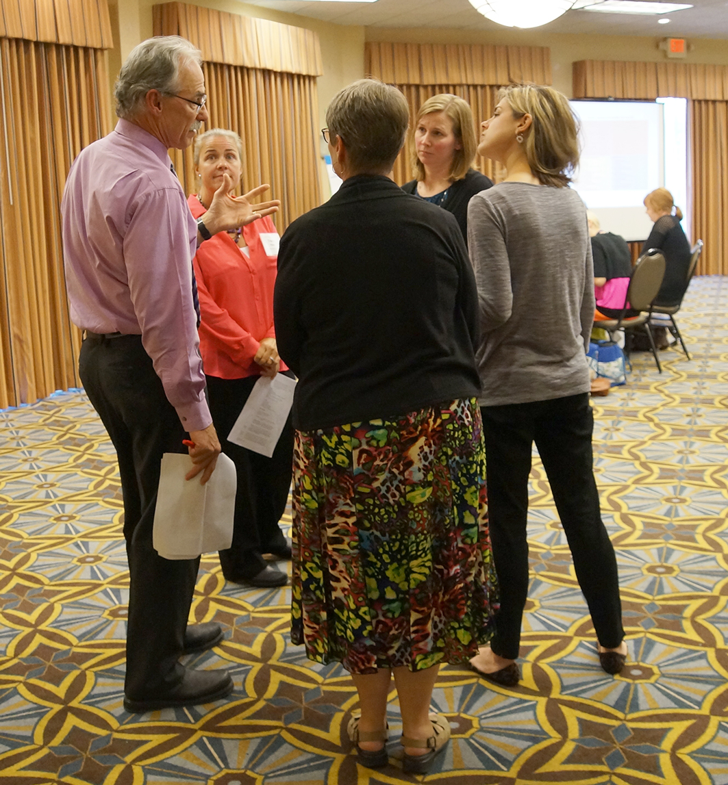 Facilitators discuss how to lead break-out groups